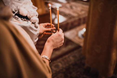 Female hands hold two burning candles in the church. Stockfoto