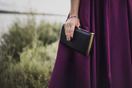 woman in a purple satin dress and a bracelet decoration on her hand holds a clutch handbag on a green natural backgrounds a black compact clutch handbag. 写真素材