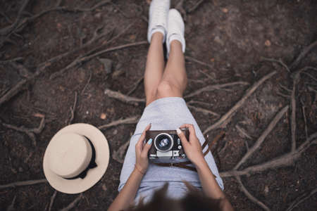 Slavic tanned fair-haired young girl with a boater hat on nature. Traveler tourist in a dark forest. constant tone of clothes. dark brown background