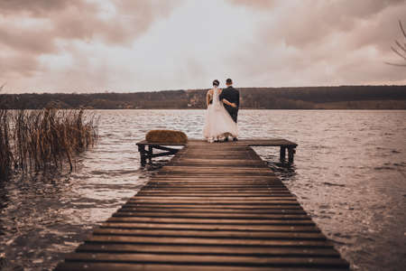 The groom in a classic suit and the bride in a white wedding dress stand in an embrace on a wooden dock look at the river. A loving couple on a wooden bridge.