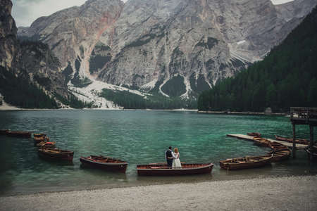 The wedding couple stands on shore of huge wide transparent turquoise aquamarine green lake in middle of high stone mountains.Brown boats float on the water.In the evening after sunset.Lago di Braies
