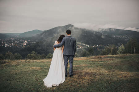 bride in a wedding dress stands her back groom in a classic suit looking at the forest in the mountains in the fog Standard-Bild