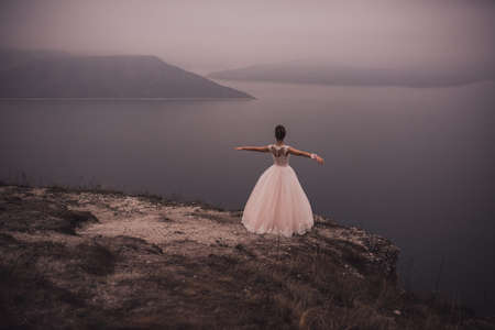 young slim beautiful woman Bride with a high Greek hairstyle and embellishment and in a White green puffy wedding dress stands on a cliff on top of a mountain. looks into the distance at sea the mount