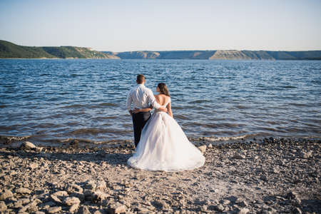 groom and bride in wedding dress stand in embrace on rocky bank near river in summer outdoors In rays of setting sun. Bakota, Ukraine