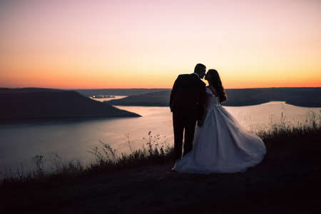 Silhouettes of bride and groom in wedding dress at night against backdrop of large lake and islands. Bakota, Ukraine