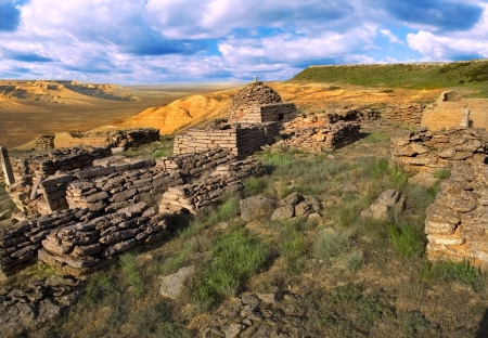 The ruins of an ancient Muslim cemetery, against the backdrop of cliffs Ustyurt in Kazakhstan Stock Photo