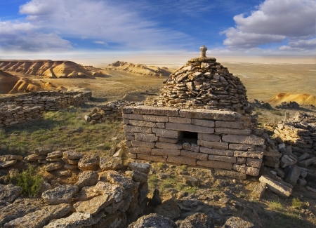 The ruins mausoleum of an ancient Muslim cemetery, against the backdrop of cliffs Ustyurt in Kazakhstan