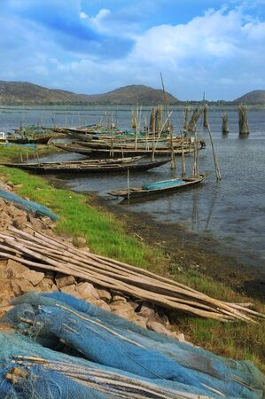 fishnets: Fishing boats and fishnets of poor Indian fishermen on the shore of a lake Stock Photo