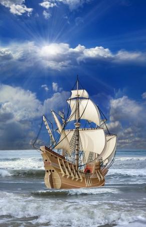 Caravel med öppna segel flyter på vågorna i havet mot molnig himmel