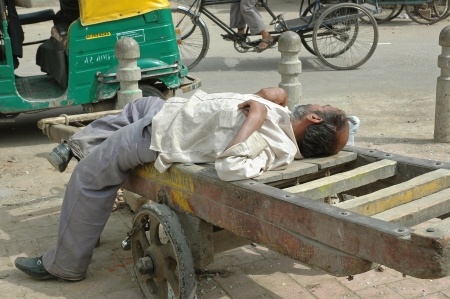 DELHI, INDIA - March 18. Unknown homeless Indian man resting in the street lying on a wooden cart on March 18, 2011 in the streets Paharganj, New Delhi, India. This is common in poor areas Delhi.