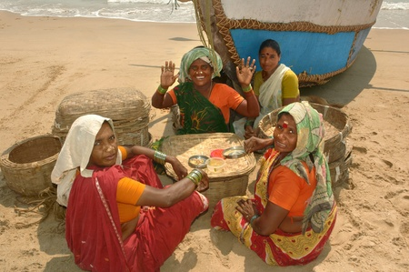 SOMPETA, ANDHRA PRADESH, INDIA - March 19  Fisherwomen women eating lunch on the beach in the shade of the boat, sitting next to baskets for carrying fish on march 19, 2012 in Sompeta, India