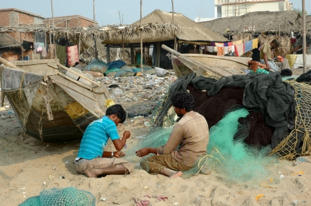 PURI, ORISSA, INDIA - March 11  Two fishermen busy mending nets on the background boats and houses of the poor fishing settlement on the beach, on march 11, 2012 in Puri, Orissa, India