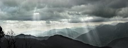 ヒマラヤの山の範囲の雲の切れ間から輝く太陽光線のパノラマ