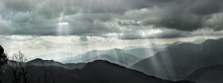 panorama över solstrålar lyser igenom molnen på intervallen i Himalaya berg