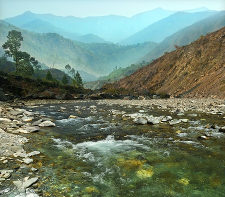 rapid flow of mountain river and colorful mountain ranges in the haze
