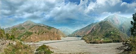 panorama of the wide watercourse river with mountain ranges in the middle  Uttarakhand, Haidakhan, Gola river