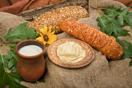 Breakfast bread and butter and milk in a clay pot on the tablecloth with flower