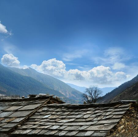 indian village: Stone roofs of houses in Indian village against the backdrop of the Himalayan Mountains
