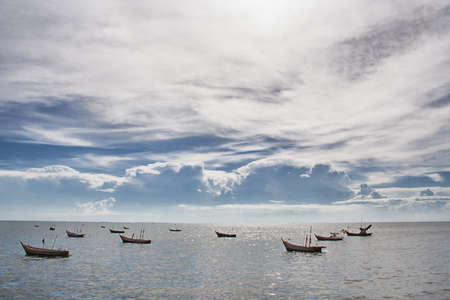 Fishermans boat among calm sea and beautiful cloudy sky Stock Photo