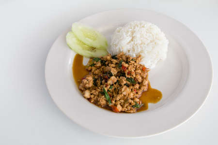 Thai Basil Chicken with rice (Pad Krapow) on white plate with cucumber