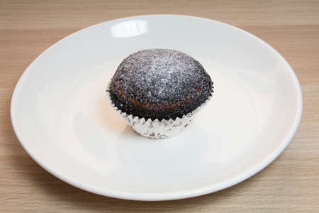 Close up on Chocolate Muffin cake with white plate on wooden Table