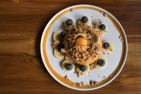 Overhead Shot Cake with Peanut Butter on top with Granola Banana and Berry on Wooden Table