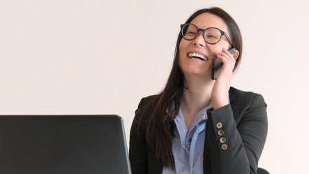 Smiling Asian business woman on smart phone Standard-Bild