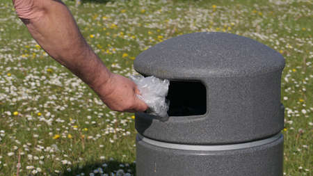 Hand and plastic bag with recycle trash can Standard-Bild