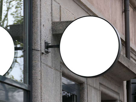 Blank round signboard on the brick wall