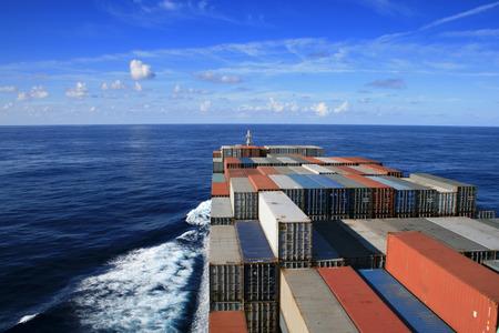 schepen: Blauwe lucht en containerschip onderweg Stockfoto