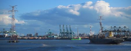 Busy cargo terminal and container vessel passing by