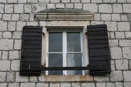 Old wooden window and brown shades