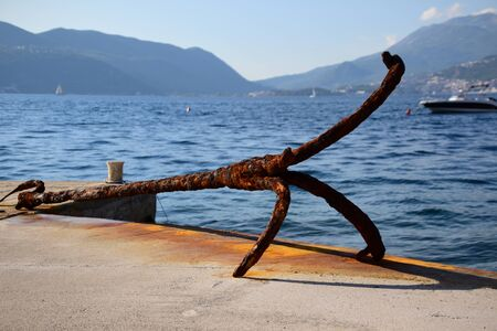 Old rusty anchor left ashore as tourist attraction. One fluke is missing. Banco de Imagens
