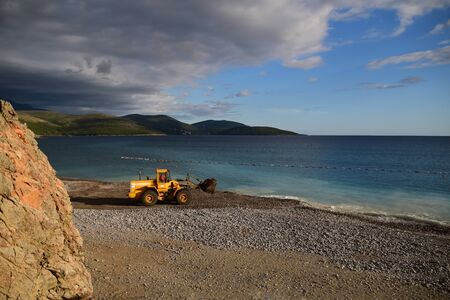 Digger working on the beach, polluting the water. Action shoot. Photo taken in Lustica Bay, Montenegro.