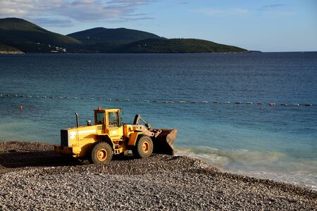 Digger throwing sand and rocks in the water to extend a beach. Water pollution. Photo taken in Lustica Bay, Montenegro. Stok Fotoğraf