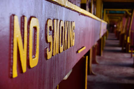 No smoking sign welded on a side of hatch coaming. Visible is main deck on container vessel.