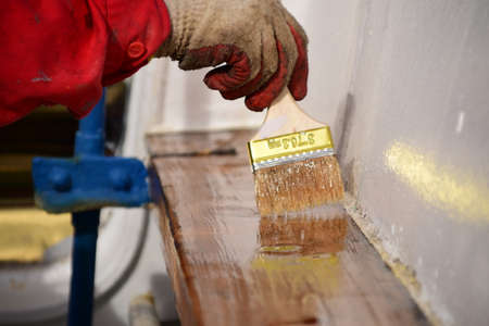 Maintenance of wooden surface on a ship requires several layers of varnish to be applied.