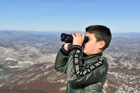 Boy at the top of the mountain observing birds with his binocular.
