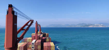 Container vessel approaching to the port of Hong Kong. Cargo cranes and container units loaded on deck.