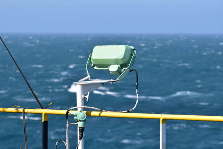 Reflector, used for illumination of deck areas on board a cargo vessel. Also called floodlight. Pointing at aft maneuvering station. Rough sea in the background. Banque d'images