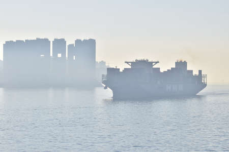 Large container vessel coming to the port of Hong Kong. Morning fog on arrival.