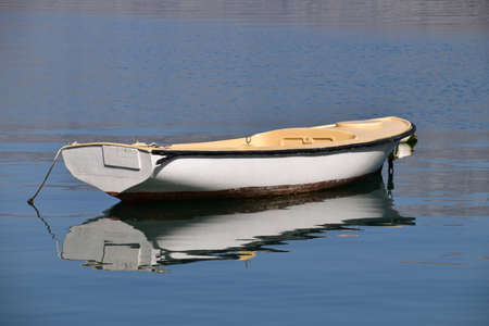 Plastic boat and reflection in calm water. Photo taken in the bay of Boka Kotorska. Banque d'images