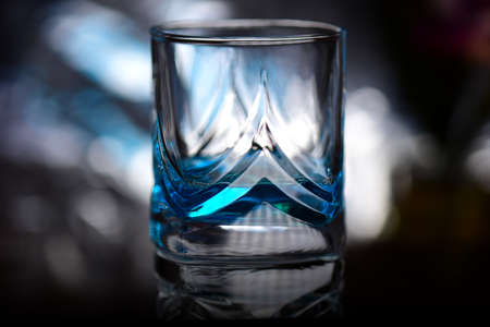 Glass with blue alcoholic drink.