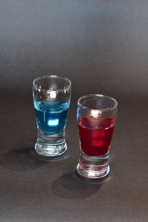 Two small glasses of alcohol drink in red and blue color. Banque d'images