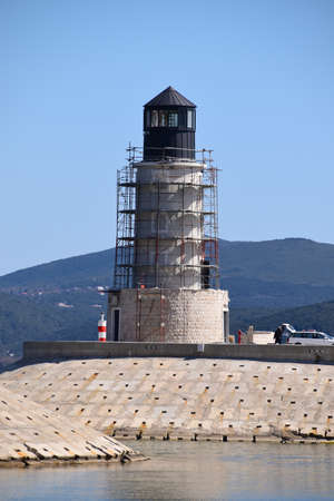 Building a new light tower at the entrance to the luxury marina. Tower is surrounded with stage or scaffoldings. Archivio Fotografico