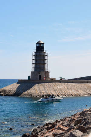 Speed boat is entering marina, passing near a light tower. Photo was taken in Lustica Bay, Montenegro.