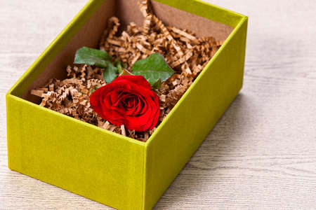 Red rose in the gift bon on wood table photo