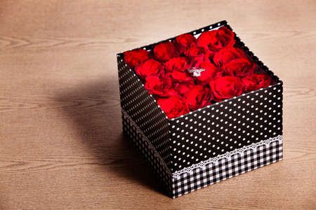 Red rose in black gift box on wood table photo