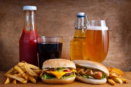 papas fritas: Comida basura, con hamburguesas, hot dogs, papas fritas franc�s, refrescos de cola, salsa de tomate y cerveza en un fondo de madera