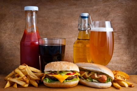 hotdog: Junk food with burger, hotdog, french fries, cola, ketchup and beer on a wooden background